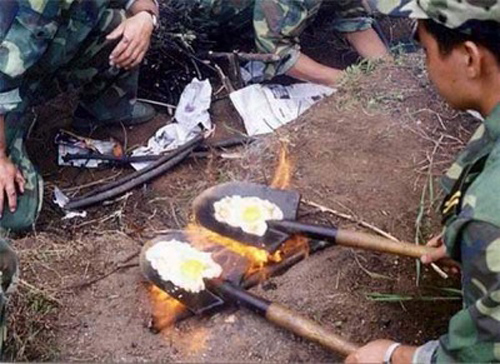 Military frying eggs on shovels in Asia, from Street Use